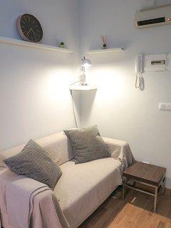 Acogedor rincón con sofá para 2 personas, lámpara retro y TV full HD.