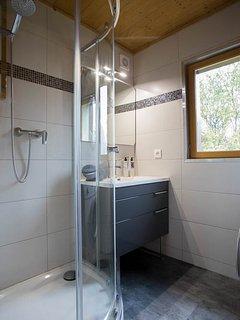 Bathroom with corner shower, sink and vanity unity, washing machine, tumble dryer