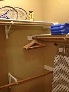 Closet with hangers, racquets, racquet balls, iron, ironing board, and swimming towels.