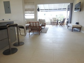 Open Plan Living Area leading to balcony/terrace overlooking gardens,pool and with sea views