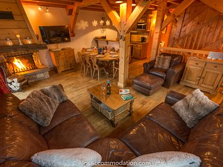 Comfortable leather corner sofa positioned in front of the warming log fire.