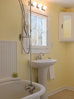 Cheerful bathroom with claw-footed tub and shower.