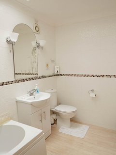 Bathroom , fully tiled with wall lights, electric extractor, wall mirror and magnifying mirror.