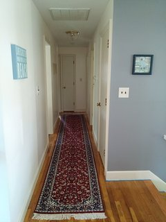 Upstairs hallway leading to the bathroom and two bedrooms.