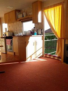 open kitchen with door leading to veranda.