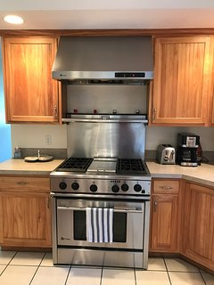 Commercial gas range with griddle and heat lamp.