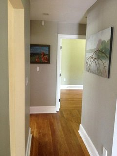 Downstairs hall from kitchen to bath, office, second living room. Beautiful local artwork on display