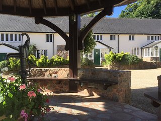 Rosemary Cottage looking onto the thatched pump house with seating area.