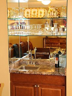 Glassed in wet bar with guest conveniences next to dining and living areas.
