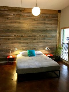 Bedroom with queen bed and wood wall treatment.
