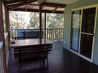Bottlebrush Cottage entrance with BBQ facilities and outdoor furniture.
