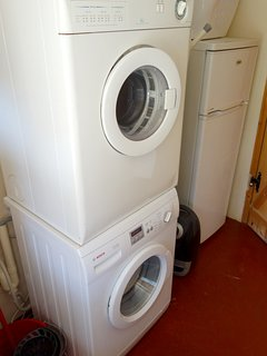 Utility room - with washer machine, dryer, secondary fridge freezer, ironing board and iron.