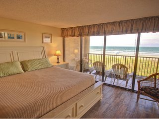 King size bed with floor to ceiling view of the beach