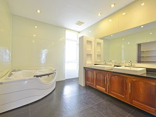 Modern spacious master bathroom with jacuzzi and his & hers sinks