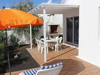 Restful rear terrace with BBQ, easy villa access via sliding doors.