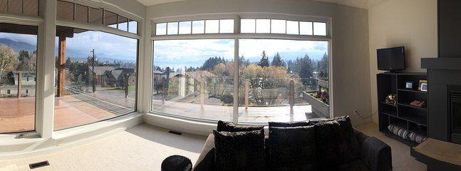 Vue panoramique sur le lac et les montagnes depuis la grande salle. Fenêtres du sol au plafond.