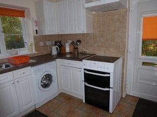 Washing machine, electric cooker/grill. Door to patio.