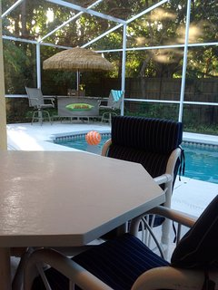 Seating in covered patio by heated pool