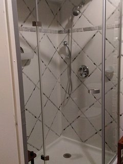 Tiled shower cabin in guest bathroom