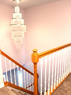 Stairs leading from entrance to second floor with crystal chandelier