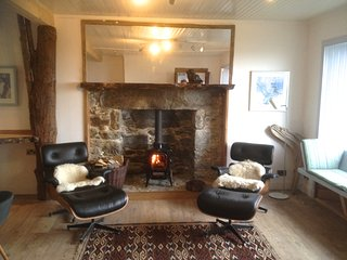 Kitchen to the right with wood burner, leather design chairs and window seats