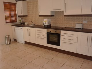 Kitchen/Dining with all modern appliances, utensils, furniture with an additional utility room.