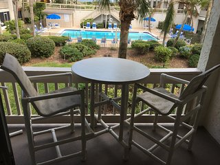 Balcony furniture over looks the pool/ocean.  Seating for 4 with 2 resin chairs.