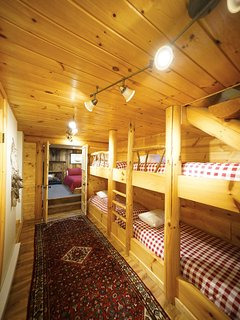 The bunk room level, complete with a queen bed nestled into its own sleeping nook, four built-in twins (bunk) beds...