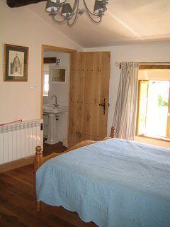 The Cottage - upstairs double bedroom with en-suite beyond and window to grounds.