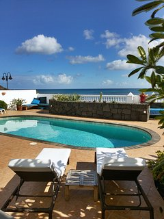 Sun loungers overlooking the pool and ocean