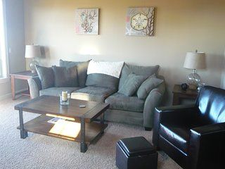 Spacious living room with oversized couch and cozy leather chairs. Deck has great view, bbq, seating