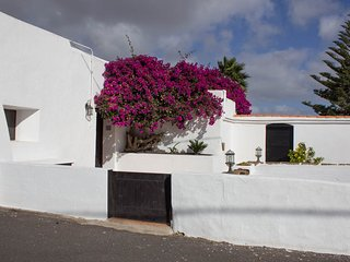front garden with large bougainvillea tree & double doors leading into the dining hall