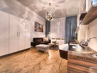 Spacious living room with comfortable sofa, flat-screen TV and working desk