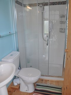 En suite shower room with large glass enclosure and power shower.