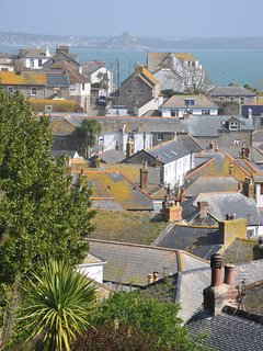 Tapestry of lichen covered rooftops in nearby Mousehole with St Michael's Mount beyond.