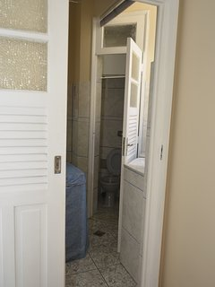 small bathroom in front of single bed