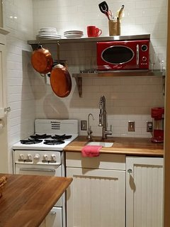Fully equipped kitchen with gas range, microwave, ice maker, refrigerator, and disposal
