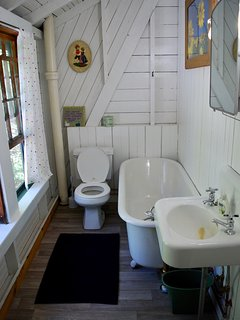 Second floor bedroom has old fashioned tub with hand shower.