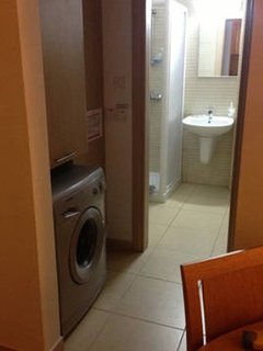 Washing machine in alcove leading to shower room