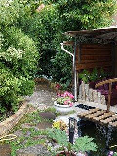 Le patio, près du petit pont, 2 canapés, table basse, aquarium...