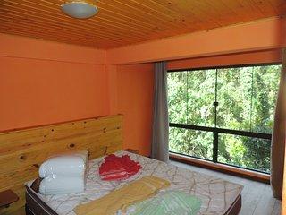 quarto de casal com cama box quenn, com vista para a mata e armário