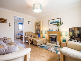 The Beach House Walk sitting room combines airy openness with cosy comfort.