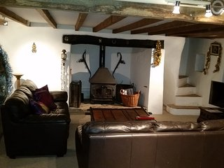 Cosy living room, with leather sofas, inglenook fireplace with log burner and 50' smart UHD TV, DVD