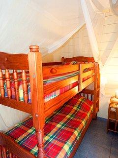 lits superposés, ventilateur et lames ventilantes, moustiquaire, porte sur jardin.