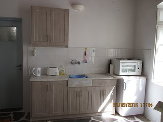 The kitchenette area with fridge, cooker, sink and units.