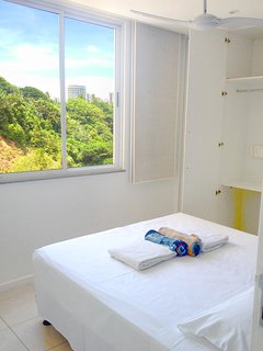 Third bedroom, with a view to the forested hill behind the apartment. Double bed and wardrobe.
