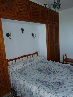 Dormitorio principal con armarios y vistas al mar y al jardín.