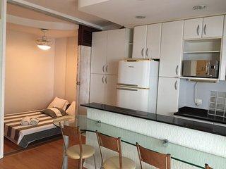 Cozinha compacta com geladeira e microondas.