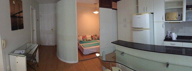 Vista da cozinha e do espaço com o sofá, que vira duas camas de solteiro ou uma cama de casal.