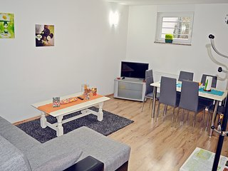 Living room with LCD TV, dining area with table for 6 people. Windows have a garden view.